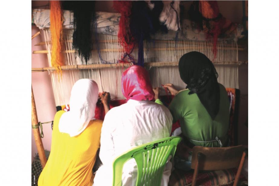 #12, femmes tissant un tapis noué dans la commune de Tighdouine (panneau de l'exposition itinérante) ©S.Gebrati